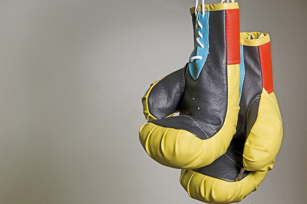 A pair of 12 oz boxing gloves hang from the ropes of a boxing ring.