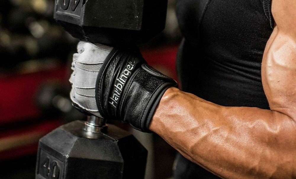 man wearing training gloves and holding a dumbbell