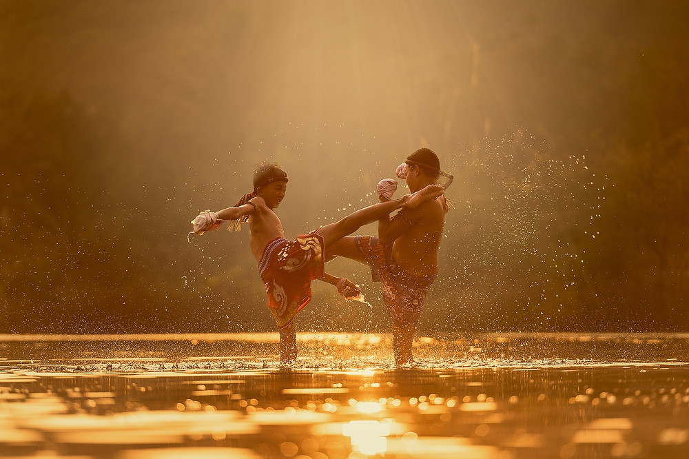 two young boys practising Muay Thai boxing in a shallow lake