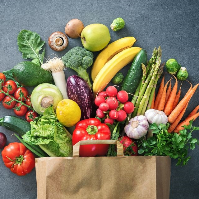 a brown paper bag surrounded by a variety of vegetables
