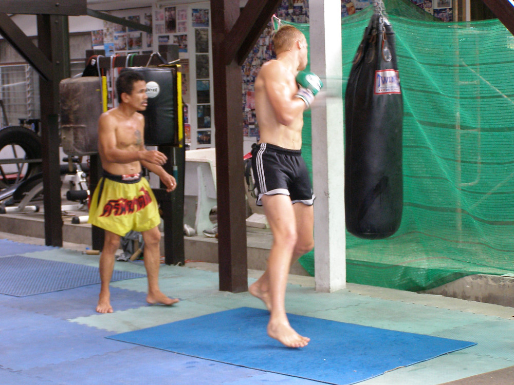 a man hitting a punch bag that hangs from a floor stand