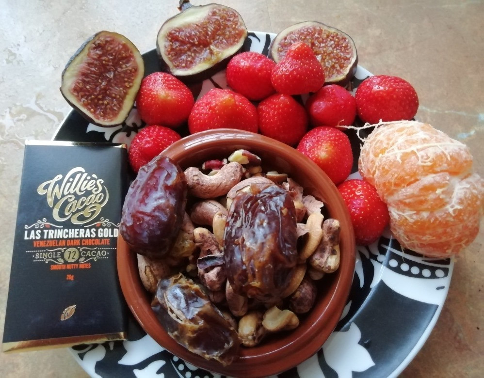 a plate containing healthy snack foods: dark chocolate, nuts, seeds, dates, figs, oranges and strawberries