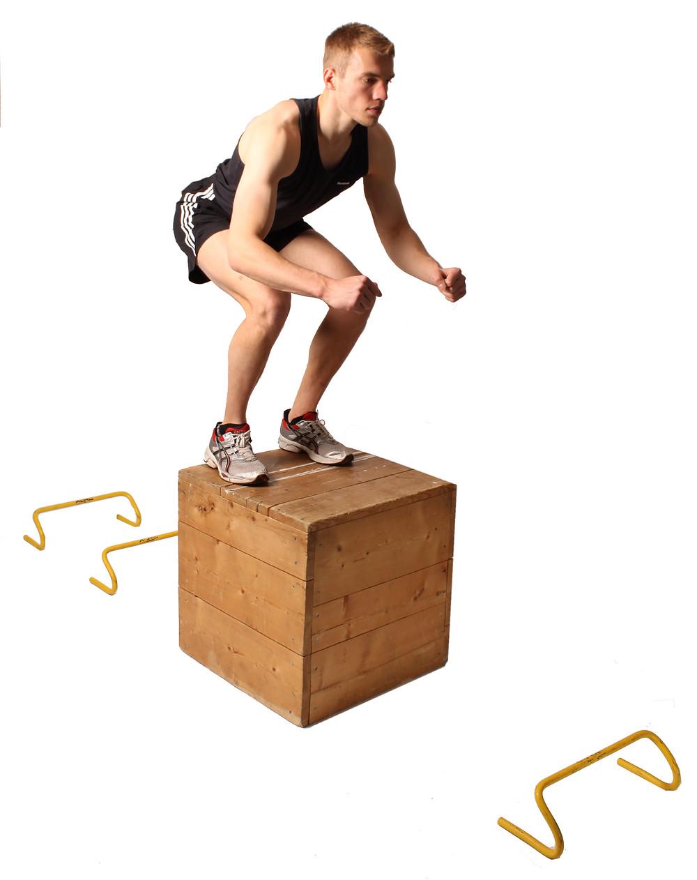 a man performing a plyometric double foot jump onto a plyometric box.