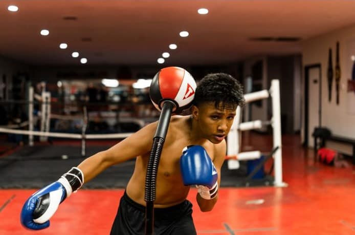 a boxer using a reflex boxing bag. He has just punched the reflex boxing bag and is now 'slipping' it.