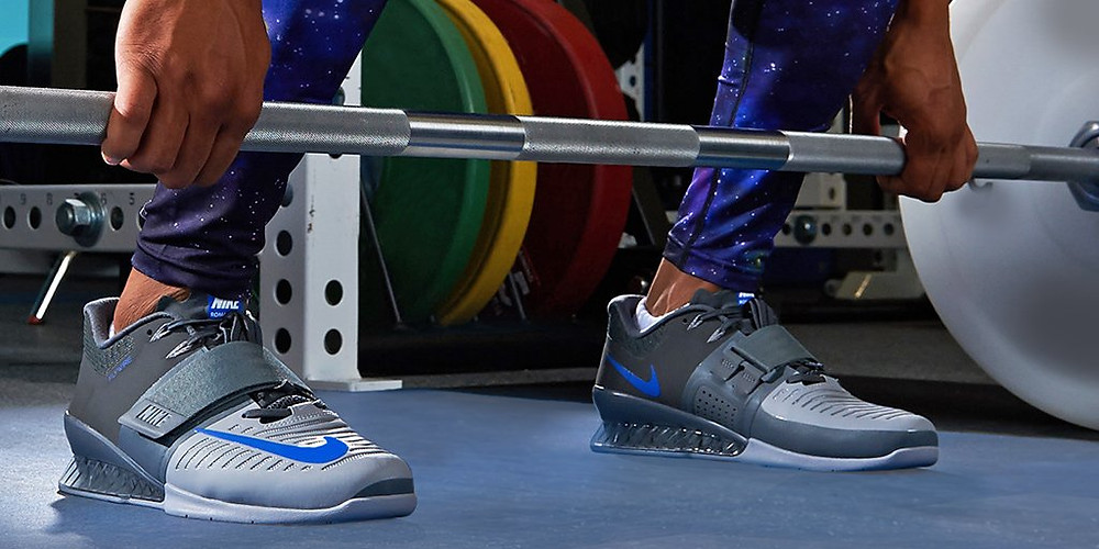 a man in a gym about to execute an Olympic lift. He is wearing a pair of deadlifting shoes so as to improve his lifting performance and training safety.