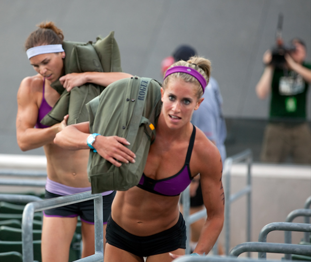 A group of CrossFit athletes completing sandbag and power bag exercises.