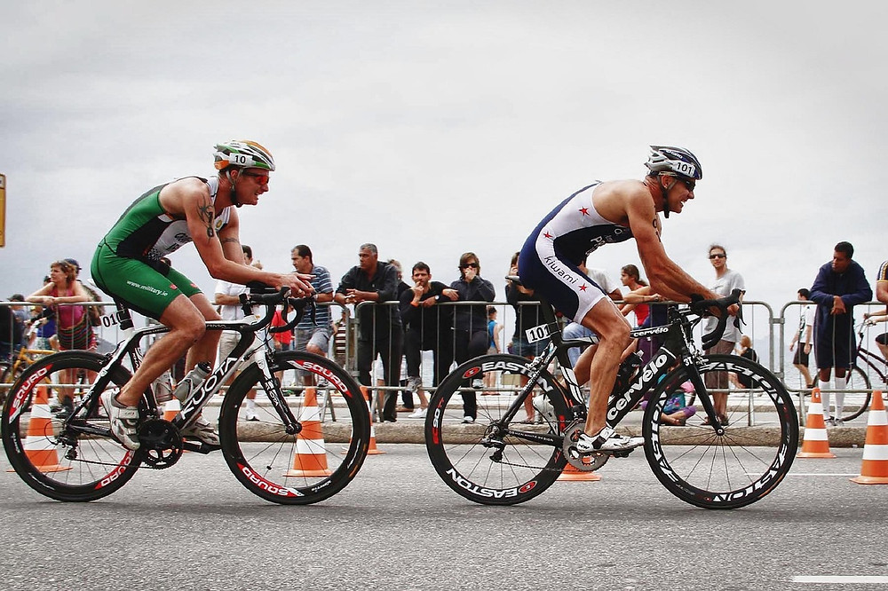 two cyclists competing in a cycling event and showing cardiovascular fitness