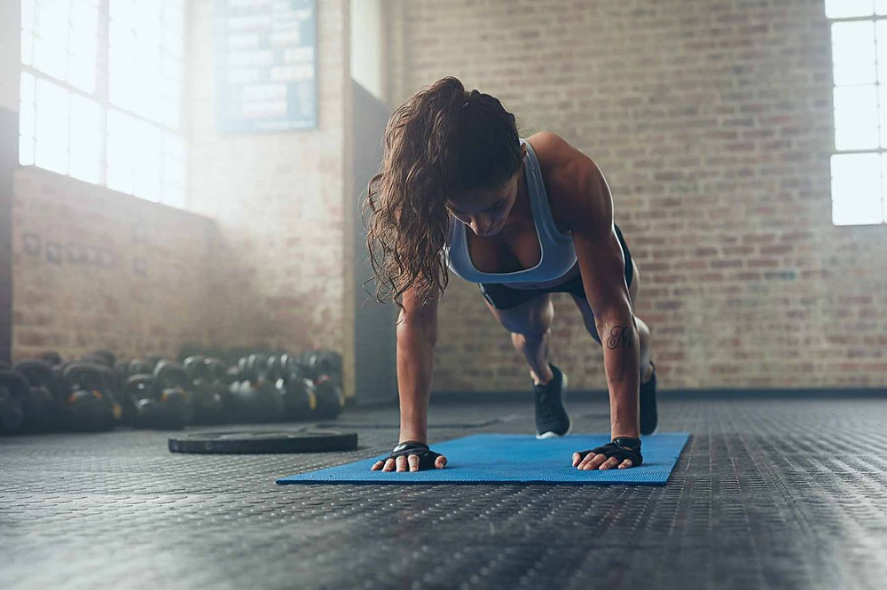 a woman at home performing press-ups to improve her fitness and burn fat and tone her muscles