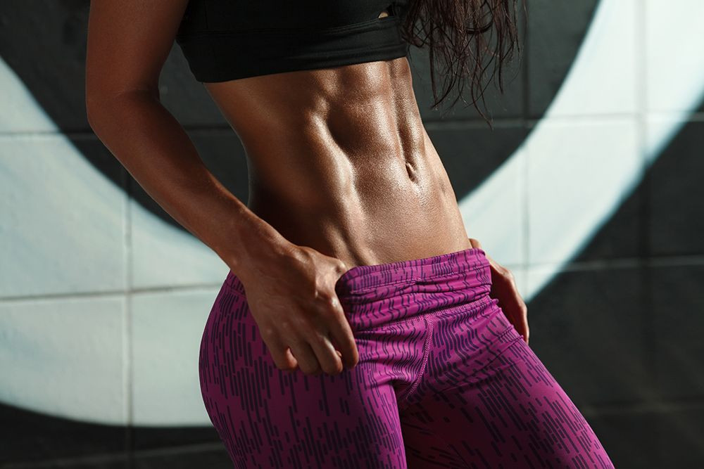 woman tensing her abdominal muscles - she is showing off her abs.
