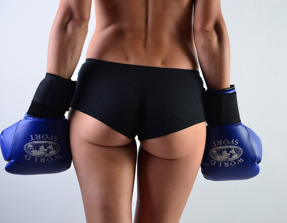 A picture of a woman wearing a pair of 10 oz boxing gloves.