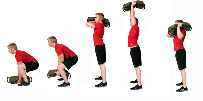 a man is working through a series of sandbag exercises. He is performing the sandbag heave.