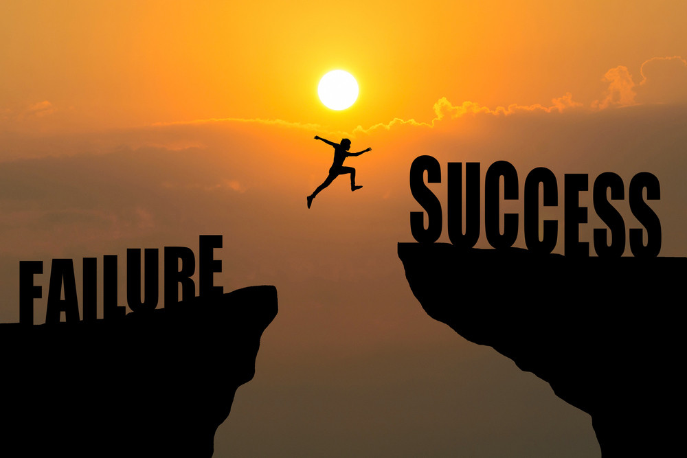 a person jumping over a cliff celebrating success