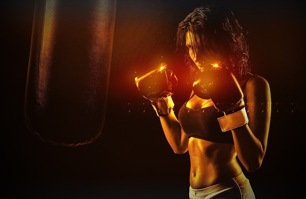 A woman standing in front of a boxing bag with her 8 oz boxing gloves on.