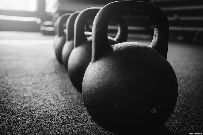 a line of kettlebells in a gym