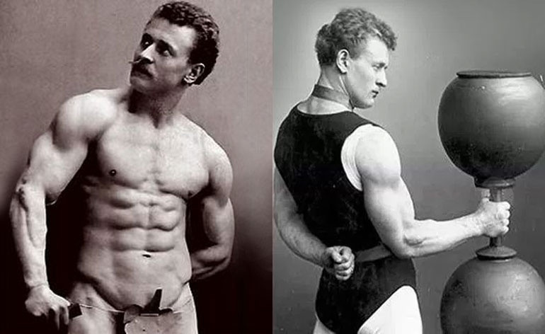 A picture of two strongmen. One is striking a muscle pose and the other is holding a huge dumbbell.
