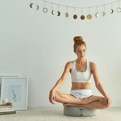 a woman seated on a meditation cusion