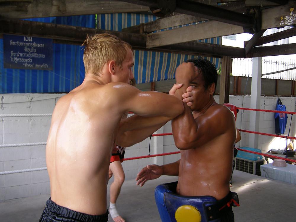 two men practising fighting skills in a boxing ring