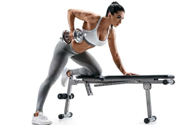 woman on a weights bench with a dumbbell performing sing arm rows