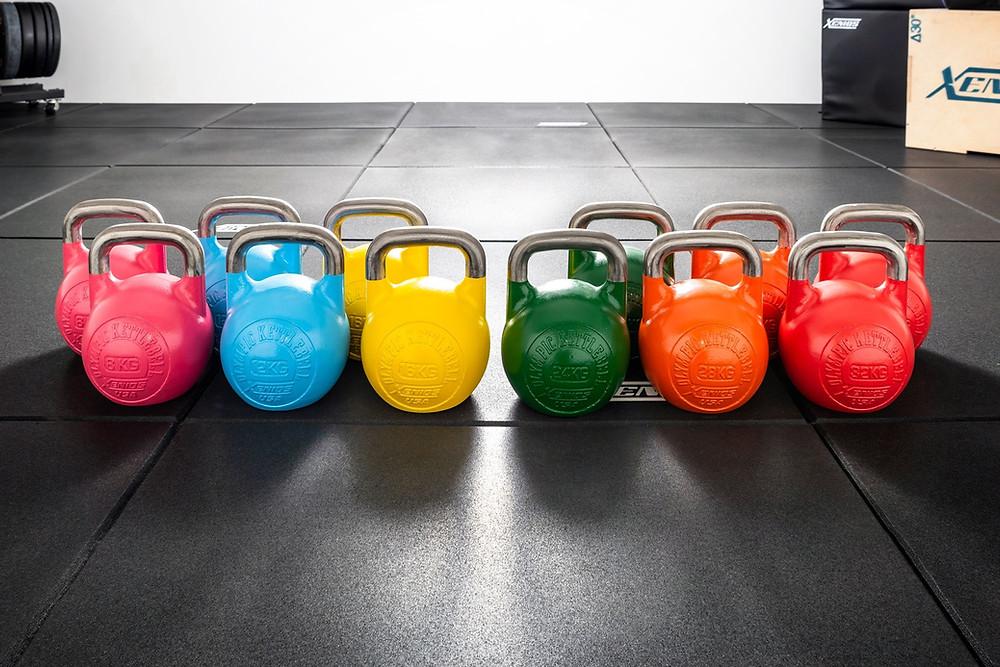 twelve competition kettlebells of assorted weights