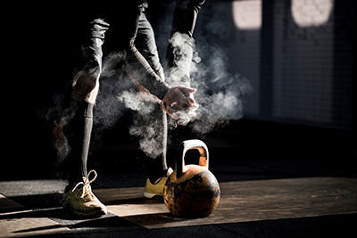 a man in a gym dusting his hands with chalk over a kettlebell