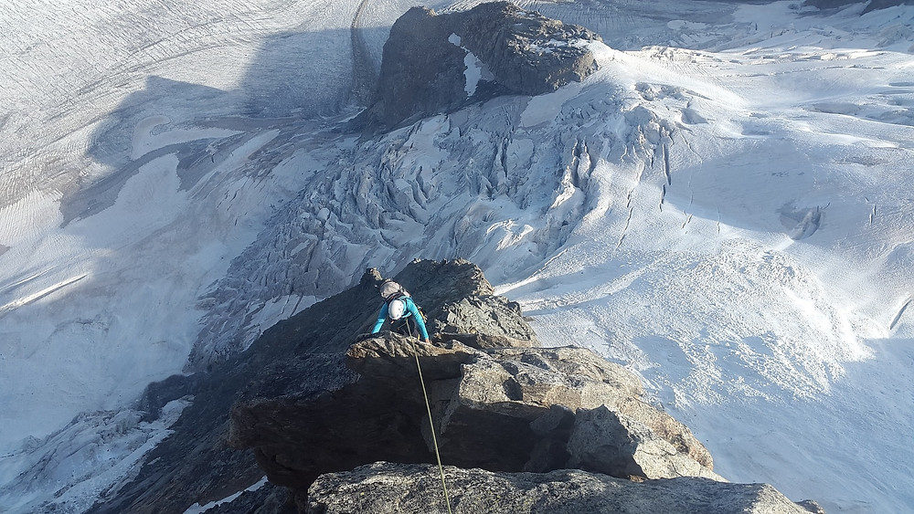 a man climbing up the side of an ice-covered mountain