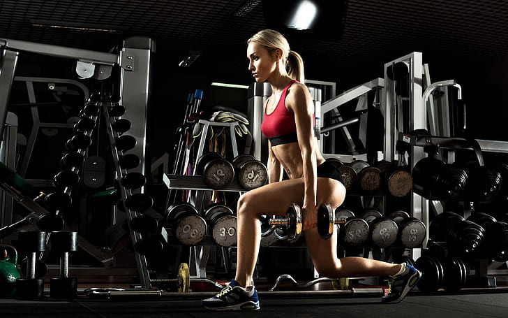 A woman is preforming a dumbbell forward lunge as part of a dumbbell leg workout.