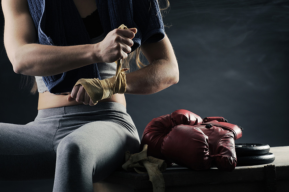 an image heading the article which reviews 5 pieces of essential boxing equipment. The image shows a woman applying boxing hand wrap. Beside her is a number of items of boxing equipment such as boxing gloves, a skipping rope and boxing shoes.