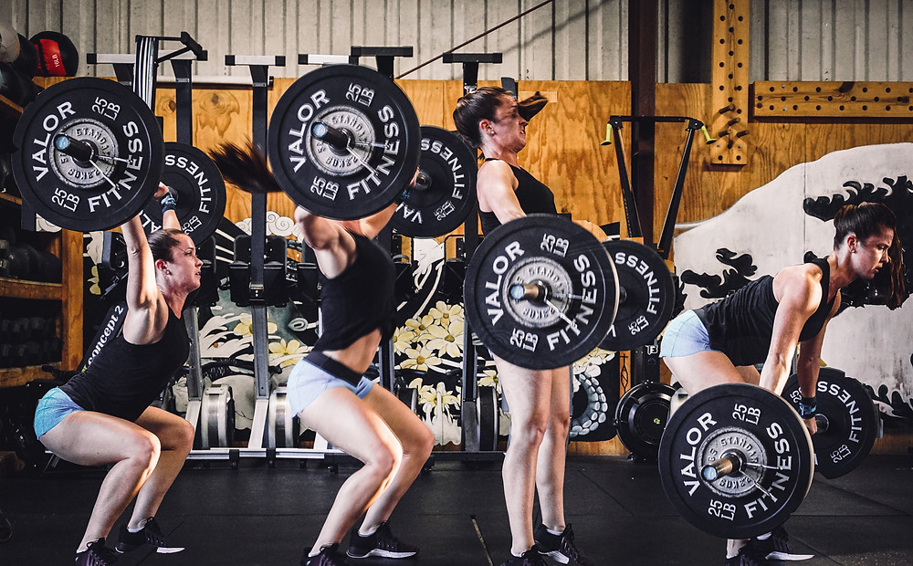 A woman workoing through a 10 minute emom workout. She is performing a CrossFit style training session. She is executing a barbell snatch.