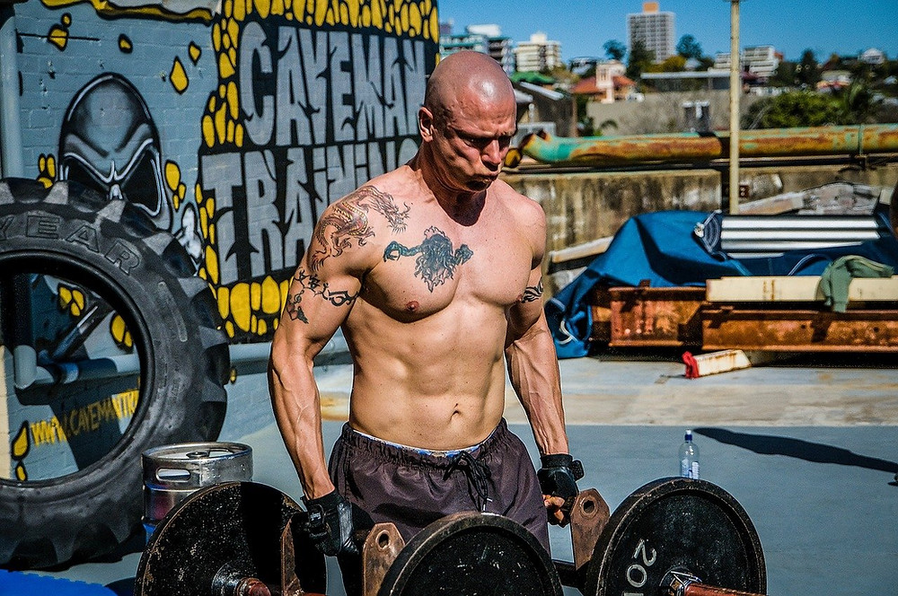 a man performing the exercise Farmers' walk as part of a 20 minute workout.