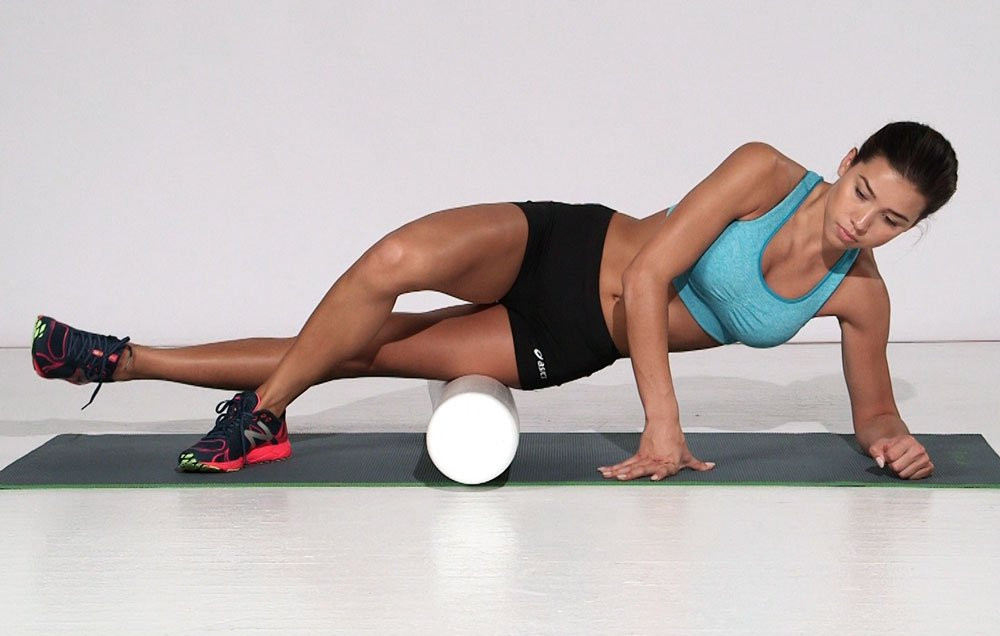 woman rolling her thigh on a foam roller