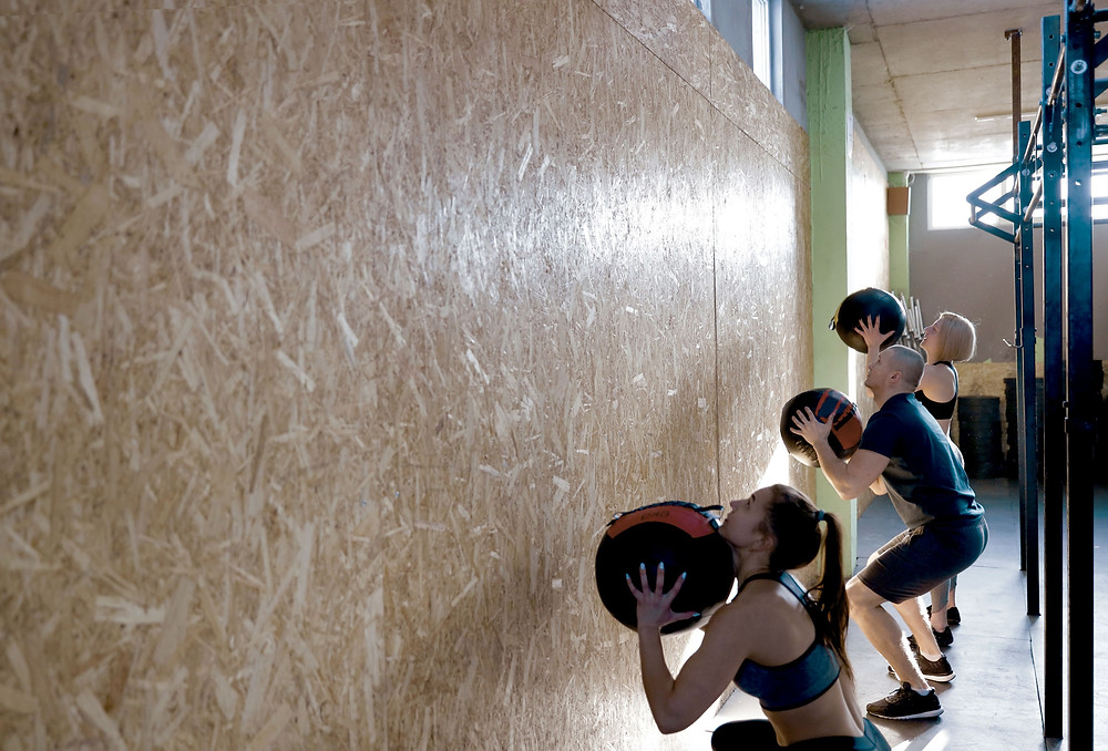 three fitness trainers throwing medicine balls against a wall
