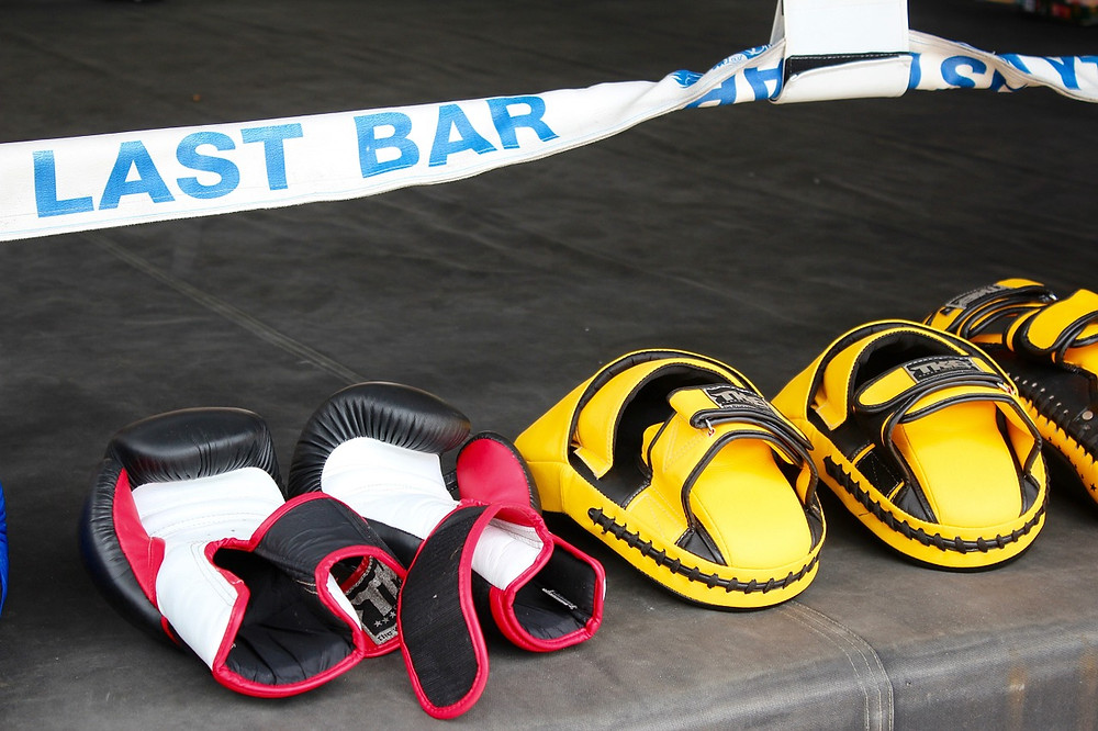 A boxing gloves and pads set have been left on the side of a boxing ring. This image heads the article that reviews the best boxing gloves and pads set.