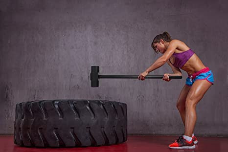 a woman hitting a tyre with an exercise hammer