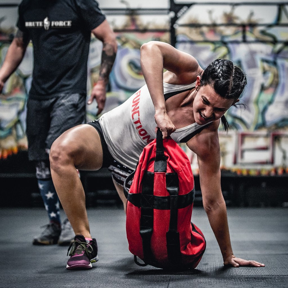 A woman taking part in a high-intensity sandbag workout. She is performing multiple sandbag exercises as part of a HIIT CrossFit circuit.