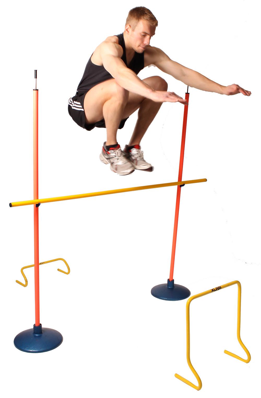 a man performing a plyometric jump over plyometric hurdles.