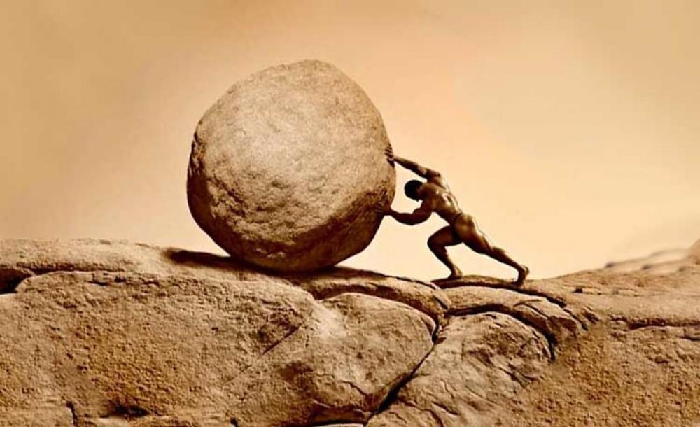 strongman pushing a huge boulder up a hill