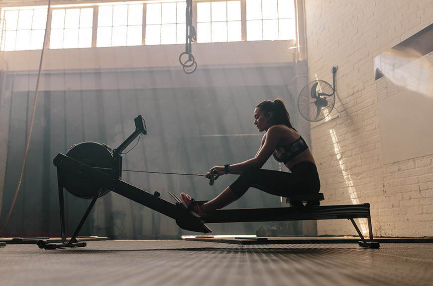 a woman sitting on a rowing machine in a gym