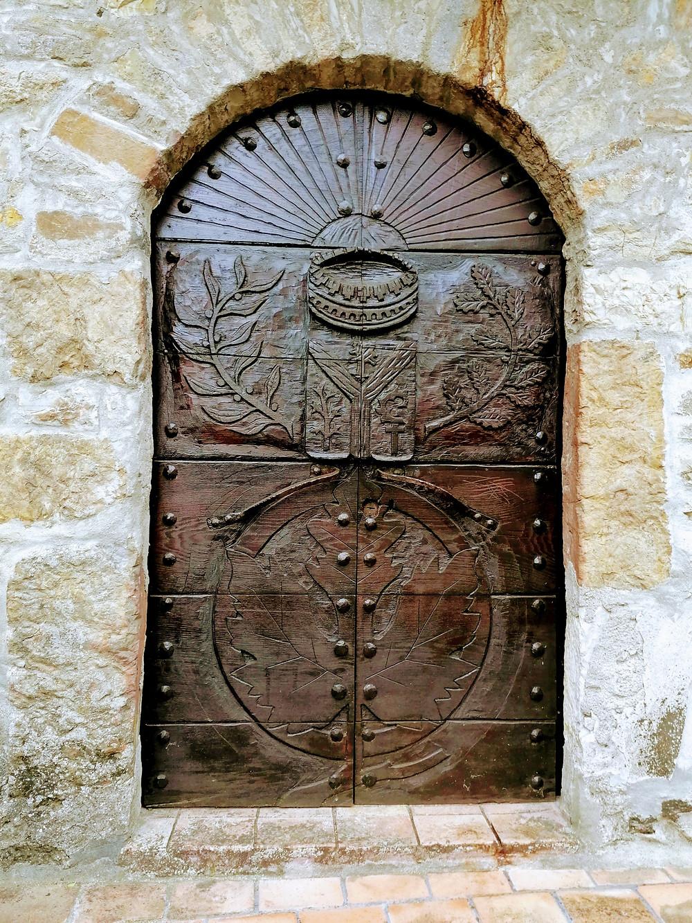 primo piano di una porta intarsiata a Brugnello, a due passi da Bobbio