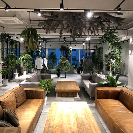 「about her」2Fはアパレルショップとアトリエ空間。緑に囲まれた広々としたソファー、天井には巨大な木根を用いたオブジェなど自然素材を用いた。可変HGレールを設置し用途によって可動出来るシステムを採用したシンプルで機能的な空間。