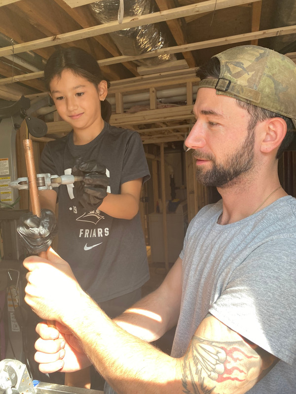 Eric teaching his daughter Victoria how to cut water piping