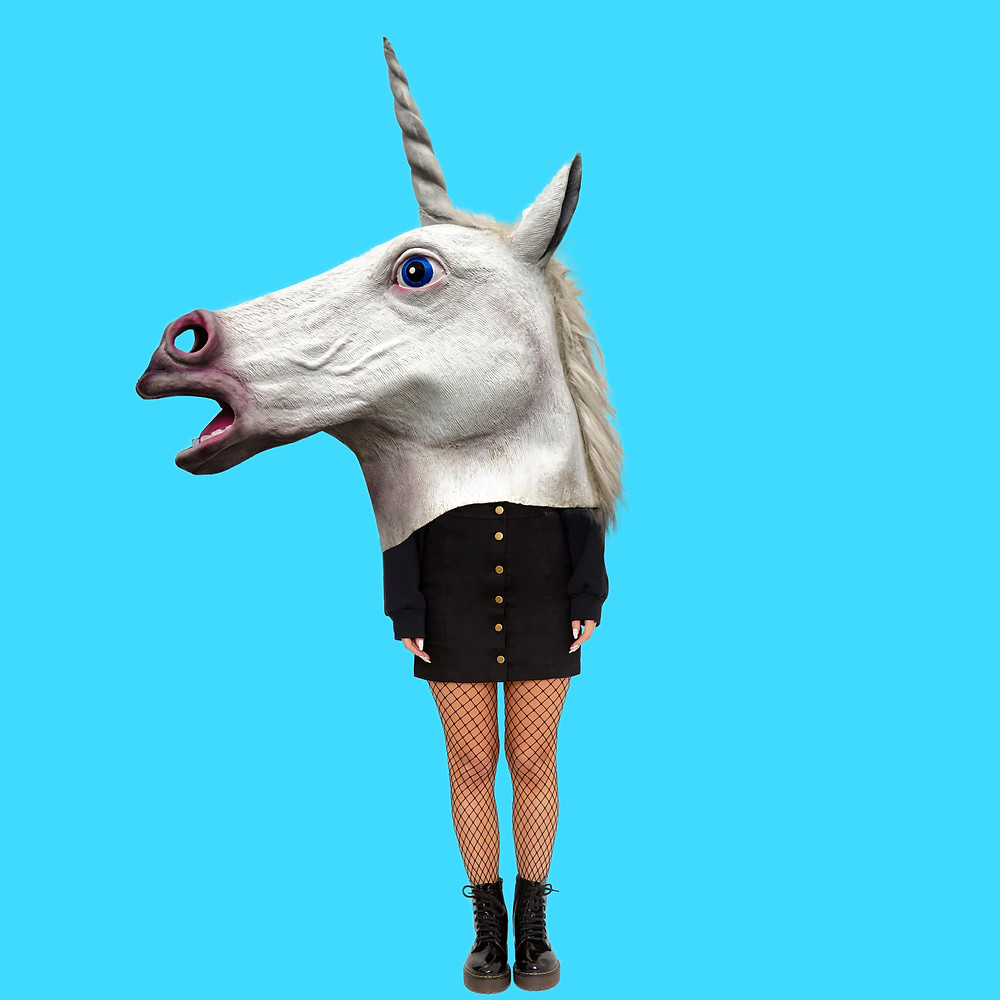 A person with a gigantic unicorn mask on with covers half their body.