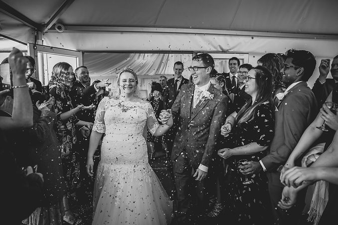 A happy couple being showered by confetti in the marquee at the Oxwich Bay Hotel