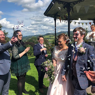 A bride and groom being showered with confetti after their humanist wedding by the bandstand in Llandeilo park