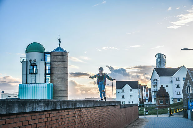 Sian Julia Jackson, Humanist Celebrant walking on a wall with views of Swansea Bay in the background
