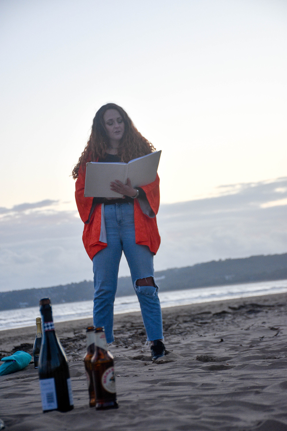 A photo of Sian Jackson delivering the Celebration of Friendship ceremony.. She is standing on Swansea Bay, you can see the sea in the background and there are bottles of beer and wine in the foreground.