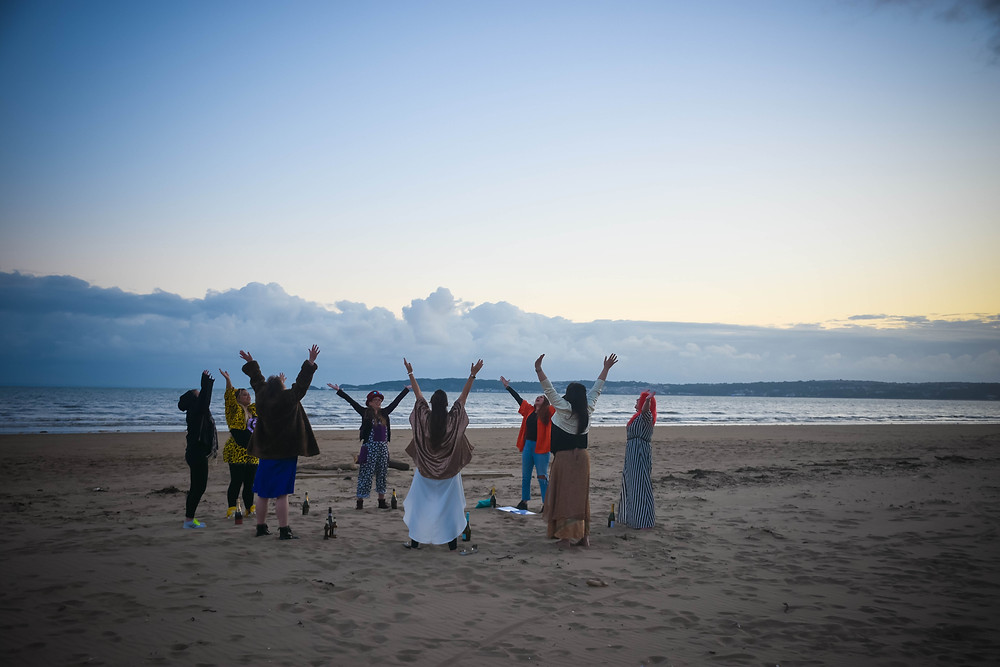 Sian and her seven friends are standing in a circle in Swansea Bay. You can see the sea in the background and all girls are holding their hands in the air as they say thank you to Swansea for igniting their friendships