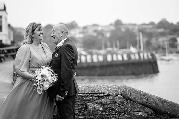 A very happy couple smiling and laughing together after ther humanist wedding in the Greenbank Hotel, Falmouth