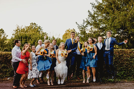 A bride, grrom and their wedding guests jumping over a broom stick