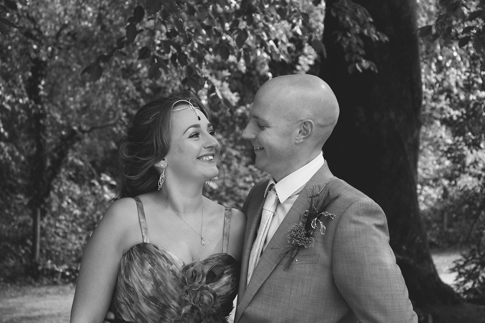 Sian Jackson humanist wedding celebrant and her husband Lee looking happily at each other and smiling on their wedding day