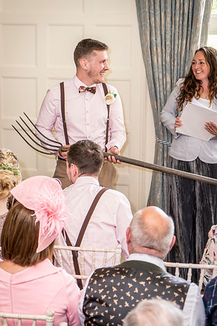 A wedding guest holding a silage fork standing next to Sian the celebrant laughing at Plas Dinam House Wales